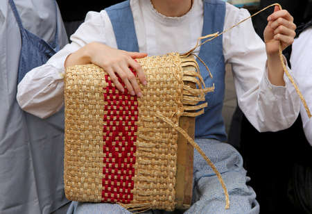 tapering: young woman with tapering fingers of the hand creates patiently a straw bag in the street
