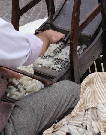 carding: Elder carder while carding wool or cotton with old wooden machine to make the cushions and mattresses