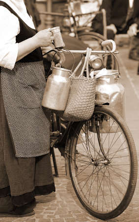 milk cans: woman carrying milk cans with a old rusty bicycle