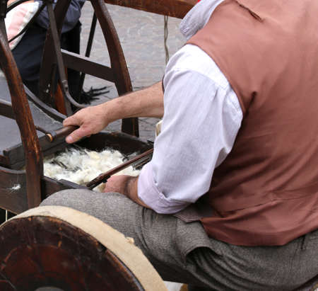 carding: Elder carder while carding wool or cotton with old wooden machine