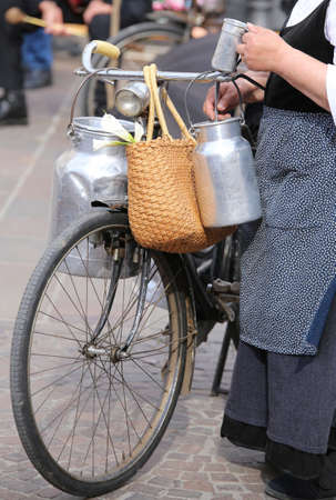 milk cans: elderly woman with very old bicycle and aluminium milk cans