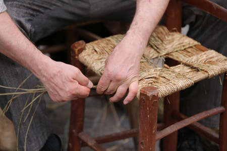 repairer: expert hands of elder repairer of chairs along the street of the city Stock Photo