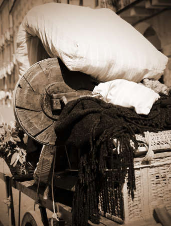old items: old cart with a mattress and other items of poor immigrant family in sepia effect Stock Photo