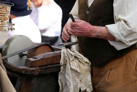 seniority: A roadside knife grinder while sharpens blade in old grindstone