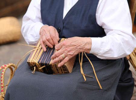 trabajo manual: manos de una mujer mayor, mientras que la creación de una bolsa de paja Foto de archivo