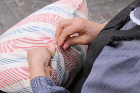 darning needle: hands of elderly woman while sewing with needle and thread the old pillow