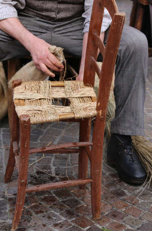 repairer: hands of a mender of chairs while repairing an old chair