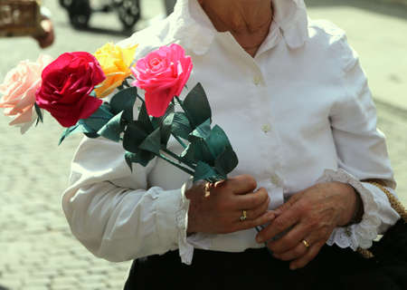 white blouse: old lady with white blouse walks with a pack of four roses in her hand