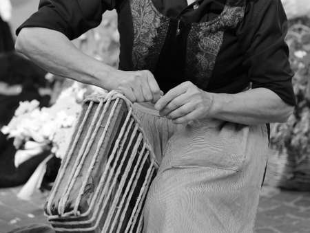 seniority: old woman working with her hands entwined the straw to create a beautiful handmade bag Stock Photo