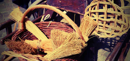 rummage: brooms of sorghum, carpet beater and wicker basket for sale at flea market Stock Photo