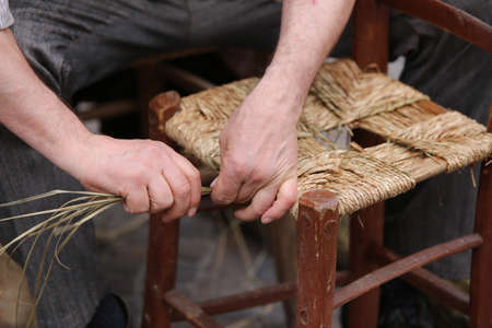adjusted: senior mender of chairs while with straw shelters the old wooden kitchen chair