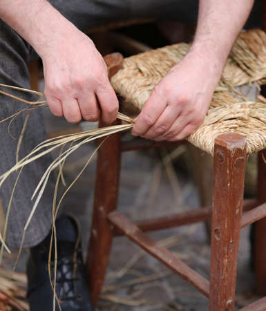 repairer: expert hands of elder repairer of chairs Stock Photo