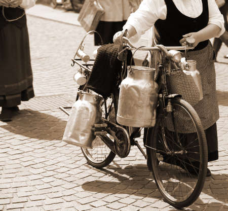 milk cans: aluminium milk cans transported on old bike of the elderly woman