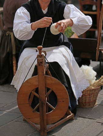 seniority: elderly woman with wooden spinning wheel while spinning a yarn and create balls of wool