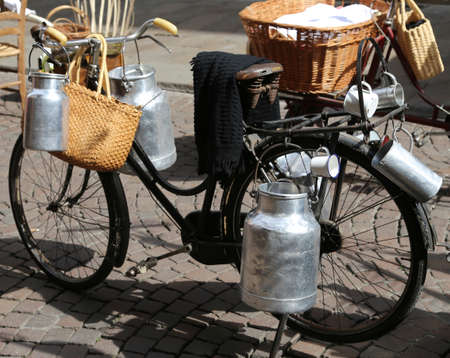milk cans: aluminium milk cans transported on old bike of the milkman
