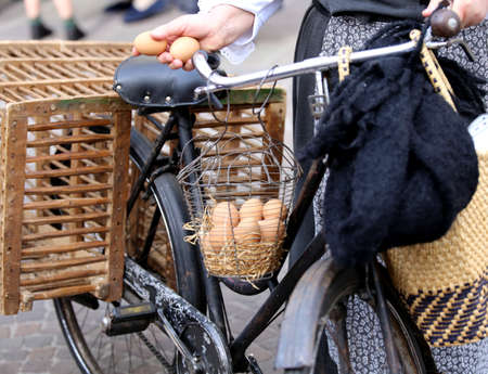 seniority: elderly woman on bike with two eggs in hand and many hen eggs in the basket Stock Photo