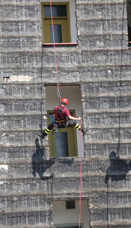 rappel: brave climber firefighter rappelling the wall during the fire drill