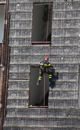 daring: bold and daring climber of firefighter climbing a wall of a house