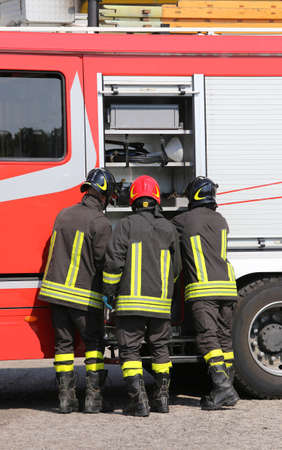 fire engine: firefighters with fire engine truck during an exercise in fire brigade station Stock Photo
