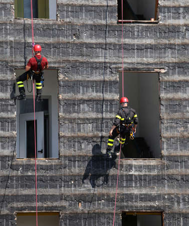 rappelling: bold and daring climbers of firefighters climbing a wall of a house during the fire drill