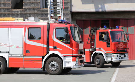two red fire engine trucks during a fire drill in the fire brigade station Stock Photo