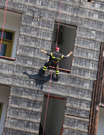 rappelling: brave climber of firefighters rappelling the wall during the fire drill