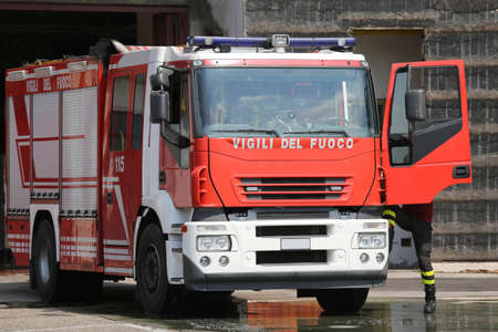 fire brigade: red fire engine truck during an exercise in fire brigade station