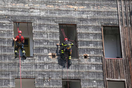 rappel: two bold and daring climbers of firefighters climbing a wall of a house during the fire drill