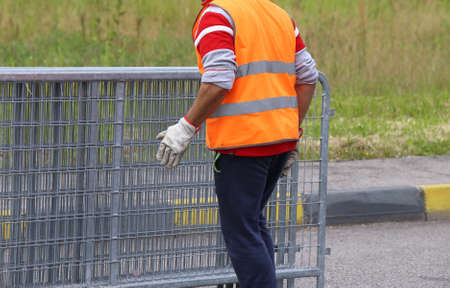 high visibility: worker with high visibility reflective jacket moves iron hurdles before the sporting event