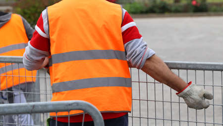 hurdles: worker with high visibility reflective jacket and gloves moves steel hurdles Stock Photo