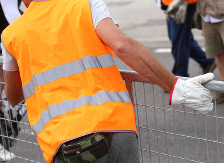 worker with gloves moves iron hurdles after the sporting event on the road Stock Photo