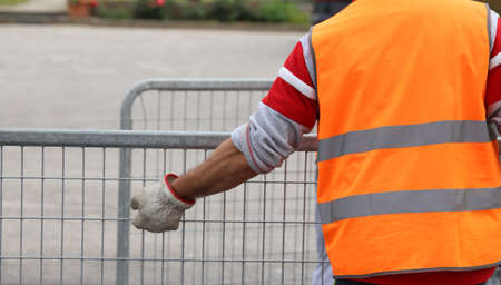 high visibility: worker with high visibility reflective jacket and gloves moves many hurdles Stock Photo
