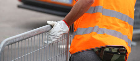 hurdles: worker with high visibility reflective jacket and gloves moves iron hurdles before the concert outdoor