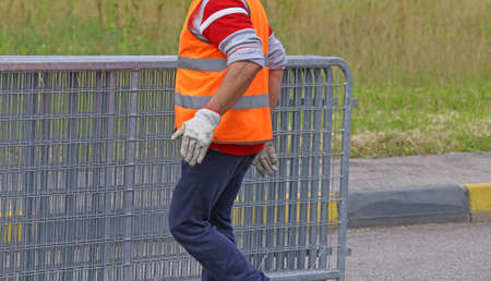 abatis: worker with high visibility reflective jacket moves iron hurdles before the concert event