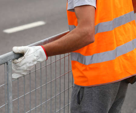 sporting event: worker with high visibility reflective jacket moves iron hurdles before the sporting event on the road Stock Photo