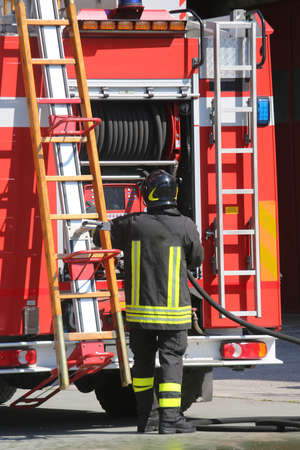 rescuer: firefighters in action take the wooden ladder from the fire truck