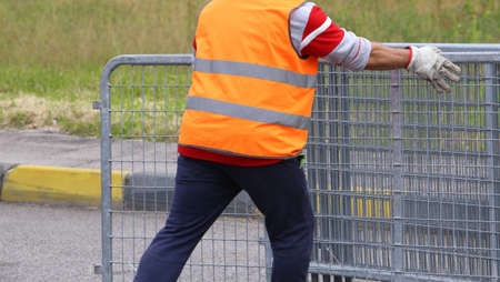 abatis: worker with high visibility reflective jacket moves iron hurdles before the sporting event