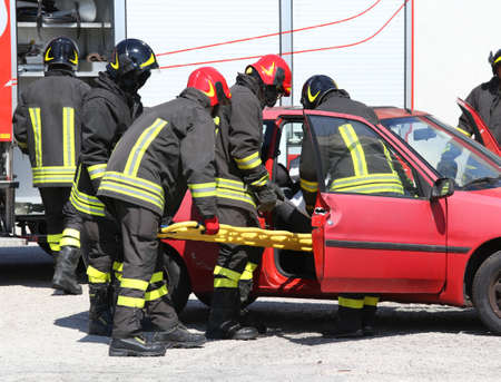 rescuer: firefighters in action and pull the injured from the car after the accident