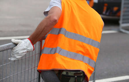 protective suit: worker with gloves moves iron hurdles after the sporting event on the road Stock Photo