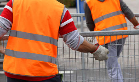 hurdles: worker with high visibility reflective jacket and gloves moves hurdles Stock Photo