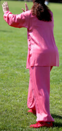 magenta dress: Tai Chi martial art Woman with pink silk dress perfectly perform the exercises in the large park