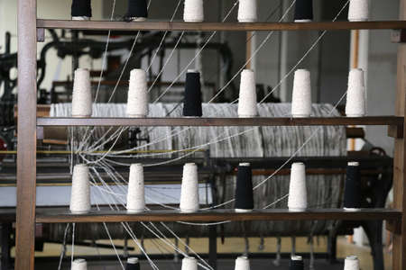 industria textil: spools of thread to spin in the old industrial weaving loom fabrics in the textile industry of the last century