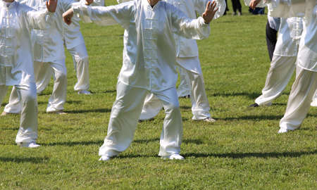 taiji: People fans of martial arts Tai Chi with white silk dress during the concentration exercises and relaxation in the public park