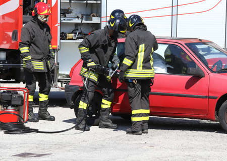 pneumatic: Firefighter opens car door with pneumatic shears after the road accident