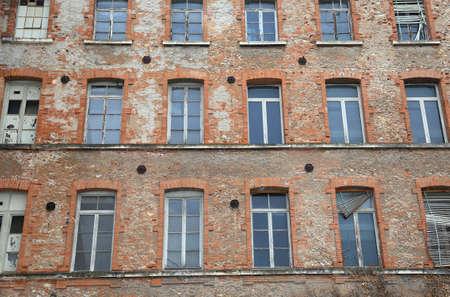 edificio industrial: antiguo edificio industrial con ladrillos rojos y ventanas rotas