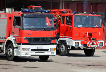 fire brigade: two truck fire engines firefighters during a fire drill training in the barracks of the fire brigade