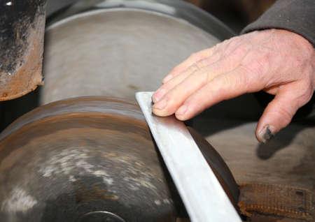 sharpen: Elder grinder with hands sharpen a blade of a knife