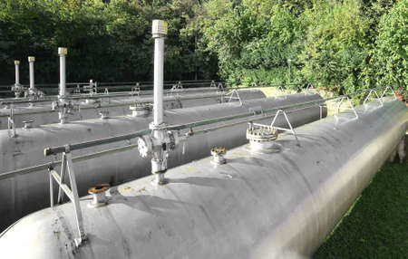 flammable: large pipeline and safety valve over the gigantic tank for storage of the flammable gas in the industrial plant