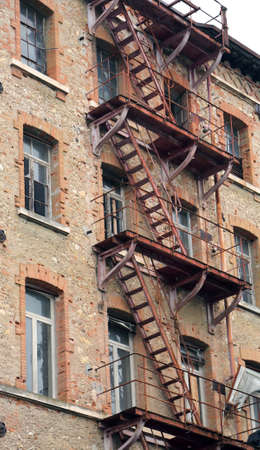 fire escape: dilapidated industrial building with rusty fire escape  and broken windows