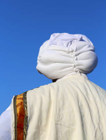 middle eastern clothing: Arab man with white turban and blue sky in background
